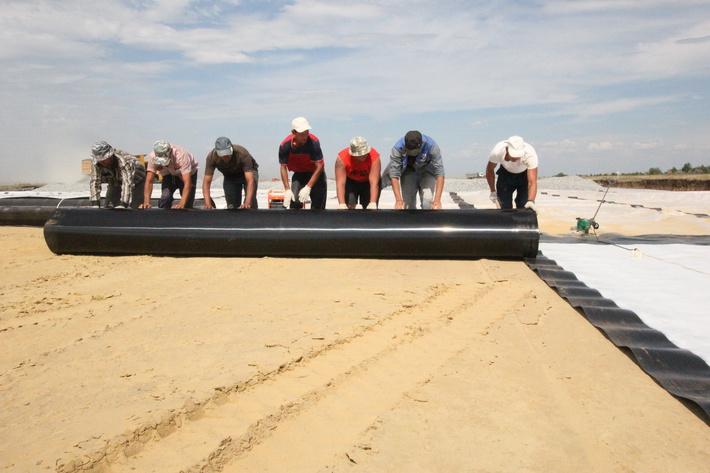 Укладка геомембраны поверх слоя песка