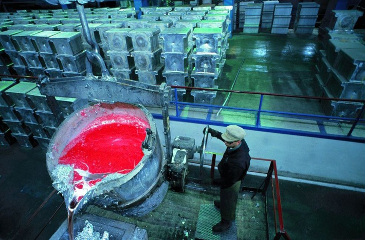 Рабочий выливает расплавленный алюминий на Богословском алюминиевом заводе «Русал»