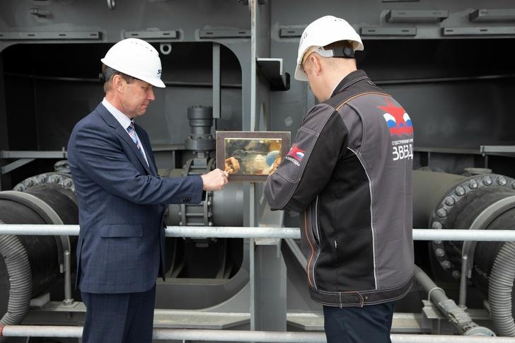 На фото: Владимир Бастин, заместитель директора инженерного центра группы «Совкомфлот» (слева), и Роман Цейгер, заместитель генерального директора по производству ССК «Звезда» (справа), устанавливают закладную доску судна.