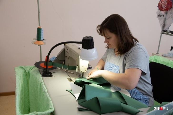 На этом фото работница сшивает детали противочумного костюма