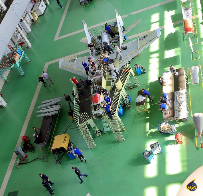 Истребитель на производственной площадке в сборочном цехе ПК №1. С правой стороны и слева лежат композитные детали для установки на планер самолета. Серая часть самолета собрана из композиционных материалов.