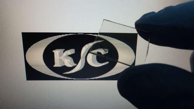 Образец прозрачного проводящего покрытия ФанНано на фоне эмблемы Красноярского научного центра
